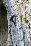Kletterer der jungen Frau, der in der Höhle klettert stockfoto