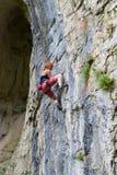 Kletterer der jungen Frau, der in der Höhle klettert stockbild