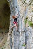Kletterer der jungen Frau, der in der Höhle klettert lizenzfreie stockbilder