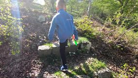 Klettern des kleinen Jungen Steintreppe im Wald stock footage