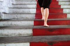 Klettern einer roten Treppe Stockfotografie