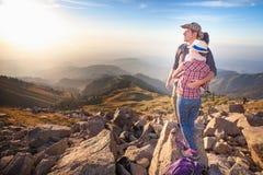 Kletternde junge Paare an der Spitze des Gipfels mit Vogelperspektive Stockfotos