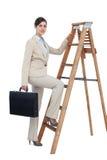 Kletternde Karriereleiter der Geschäftsfrau mit Aktenkoffer und dem Schauen Stockbild