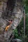Kletternde Klippenwand des jungen athletischen männlichen Kletterers Kopieren Sie Platz auf dem Recht stockfotografie