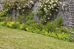 Kletternde Rosen auf Gitter in einem ummauerten Häuschen arbeiten im Garten lizenzfreie stockfotos