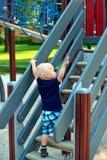 Kletternde Schritte des kleinen Jungen am Spielplatz Lizenzfreie Stockfotos