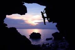 Kletternder Felsen des Fotografen in der Höhle nahe dem Strand mit dem Kayak fahren Lizenzfreie Stockfotografie