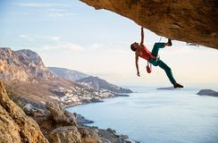 Kletternder herausfordernder Weg des kaukasischen Mannes in der Höhle bei Sonnenuntergang lizenzfreie stockfotografie