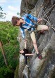 Kletterndes Felsentrekking der glücklichen Frau draußen Sorgloser lächelnder Wanderer ihr Freund Freundliche Handreichung stockfoto