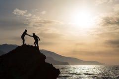 Kletterndes Wandern der Teamwork-Paare mit der Handreichung stockbild