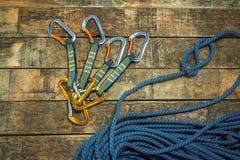 Kletterseil und carabiner auf hölzernen Brettern Stockfoto