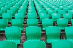 Kleuren plastic leunstoelen op stadiontribune Stock Foto's
