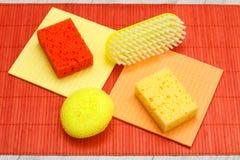 Kleuren synthetische sponsen, microfiber servetten en borstel voor het schoonmaken op bamboe royalty-vrije stock afbeelding