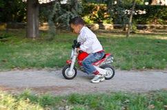 Kleurenbaby met stuk speelgoed motorfietsen Royalty-vrije Stock Afbeelding