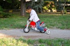 Kleurenbaby met stuk speelgoed motorfietsen Royalty-vrije Stock Afbeeldingen
