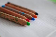 Kleurende kleurpotloden op een stuk van document Stock Afbeelding