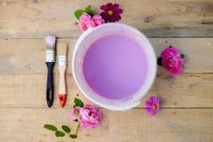 Kleurenkom met lilac verf op houten raad, bloemen Stock Foto's
