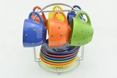Kleurenkoppen met schotels worden geplaatst die Stock Foto