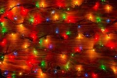 Kleurenlichten van een slinger op houten achtergrond Stock Foto's