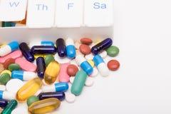 Kleurenpillen en capsules naast pillenorganisator Stock Afbeeldingen