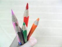 Kleurenpotloden door één enkele hand worden gehouden die Stock Fotografie