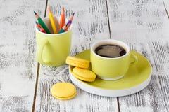 Kleurenpotloden in een groene kop met groenachtige mok koffie Royalty-vrije Stock Afbeeldingen