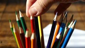 Kleurenpotloden in een schrijven-glas Trek met kleurpotloden op Witboek en een houten lijst Houten retro lijst stock video