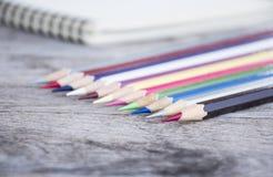 kleurenpotloden en nota Stock Foto's