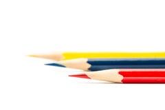 Kleurenpotloden, geel, blauw, rood, op wit worden geïsoleerd dat Stock Foto