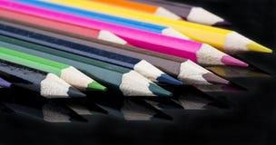 Kleurenpotloden met bezinning over zwarte achtergrond Stock Fotografie