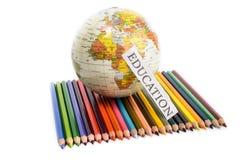 Kleurenpotloden met bol en onderwijsnota Stock Afbeelding