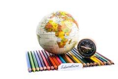 Kleurenpotloden met bol, kompas en onderwijsnota Royalty-vrije Stock Foto's