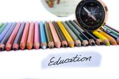 Kleurenpotloden met bol, kompas en onderwijsnota Stock Afbeelding
