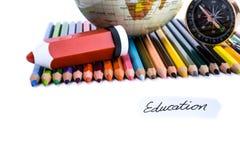 Kleurenpotloden met pen, bol, kompas en onderwijsnota Royalty-vrije Stock Foto