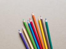 Kleurenpotloden op bruine achtergrond Royalty-vrije Stock Foto's