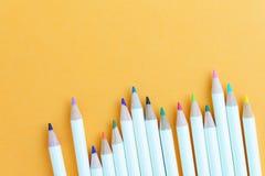 Kleurenpotloden op gele document achtergrond met exemplaarruimte die a gebruiken Stock Fotografie