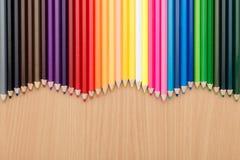 Kleurenpotloden op houten lijst voor achtergrondgebruik stock afbeeldingen