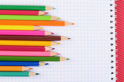 Kleurenpotloden op papier met notitieboekje Stock Foto's