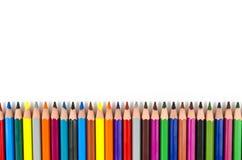 Kleurenpotloden op wit op een rij worden geïsoleerd dat Stock Afbeeldingen