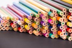Kleurenpotloden op zwarte oppervlakte Stock Foto