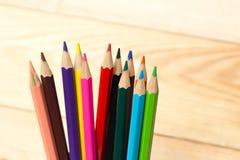 Kleurenpotlood op houten lijstachtergrond Stock Afbeeldingen