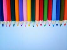 Kleurpotloden bij de bovenkant op een witte achtergrond stock afbeeldingen