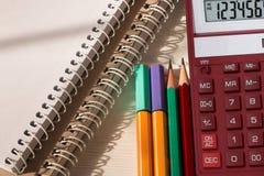 Kleurpotloden, Desktopcalculator en notitieboekjes op witte houten lijst De levering van de school en van het bureau Hoogste meni royalty-vrije stock afbeeldingen