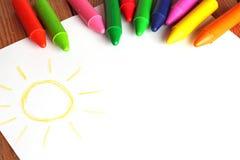 Kleurpotloden die op een document met de geschilderde tekening van kinderen liggen Stock Foto