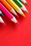 Kleurpotloden die in rij op rode achtergrond liggen stock afbeelding