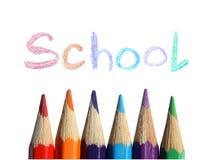 Kleurpotloden en de met de hand geschreven woordschool op witte achtergrond Stock Afbeeldingen
