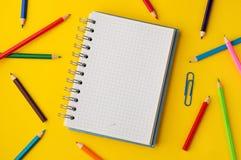 Kleurpotloden en geregelde document nota over gele achtergrond Stock Foto