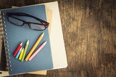 Kleurpotloden en glazen op houten lijst, onderwijsconcept Stock Afbeeldingen