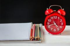 Kleurpotloden en notitieboekjes op een lijst met de wekker De levering van de school en van het bureau Front View stock fotografie