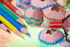 Kleurpotloden en spaanders potloden op een regenboogachtergrond Kleuren van regenboog stock foto's
